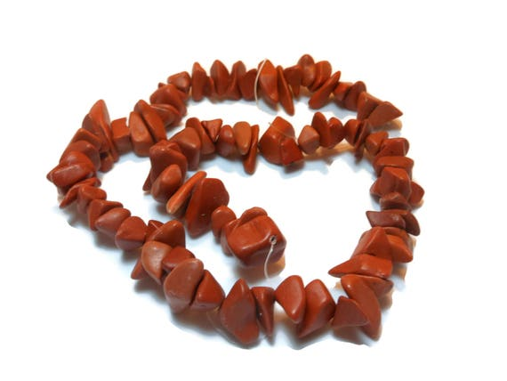Bead, red jasper (natural), extra-large chip, sold per 15-inch strand, range from medium to gigantic with an average size of extra-large