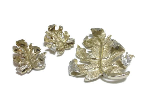 "Sarah Coventry brooch and earrings, 1960's ""Windfall"" line, gold tone with silver tips, turning leaf pin set, clip earrings"