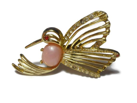 Jelly belly hummingbird brooch, gold hummingbird with pink lucite belly, red rhinestone eye and clear rhinestone embellishments, bird pin