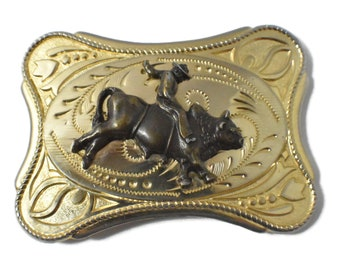 Bull rider belt buckle, rodeo bronze cowboy riding bull attached to gold decorative belt buckle with rope frame