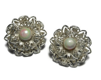 Opalescent earrings, white pearly opalescent centers with petals of silver filigree grace these floral clip earrings