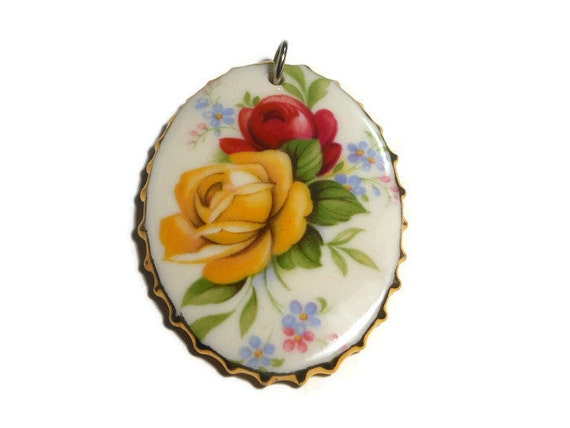 Hand painted floral pendant, yellow and red roses on  ceramic oval framed in gold painted scallops, signed Mela or Meta