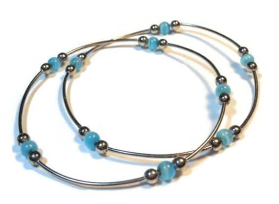 Set of two silver plated bangles with light blue cat's eye glass beads vintage