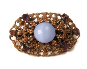 1940s Coro brooch, blue moonglow cabochon brooch with filigree scroll work and amethyst rhinestones, gold tone