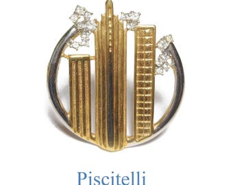 Piscitelli skyline brooch, gold buildings with rhinestone accents in a silver circle, silver and gold tone gloss matte finish