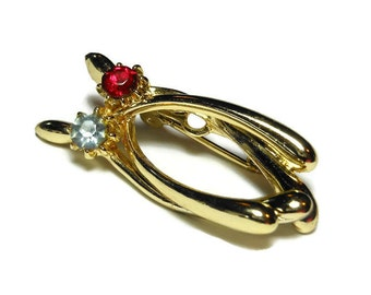Wishbones brooch, gold tone lucky double wishbones pin with a red rhinestone and a blue rhinestone, looks like a stylized cat