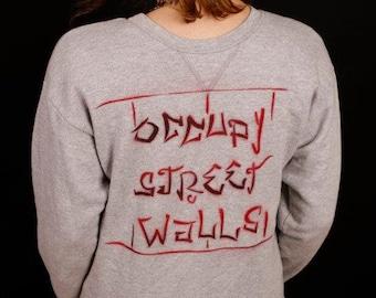 "Gray Sweatshirt with ""Occupy Street Walls"" Slogan"