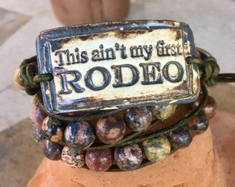 """Handmade leather wrap bracelet with red leopardskin jasper beads and pottery cuff """"This ain't my first rodeo"""" focal, pistol design button"""