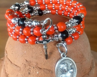 Handmade 5 decade rosary wrap bracelet in your team colors. Memory wire cuff bracelet with five decades, crucifix and St. Sebastian charm