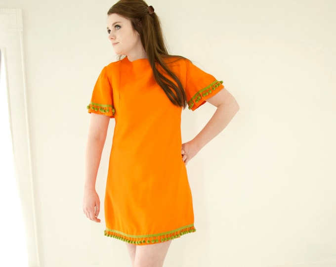 Vintage orange mini dress, green pom-pom trim, short flutter bell sleeves, bright colorful go-go 1960s mod 1970s retro M L