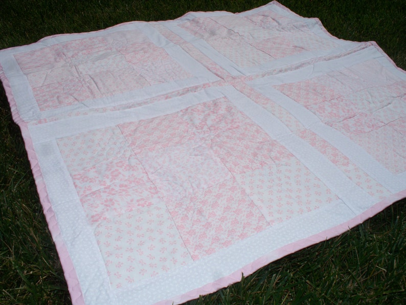 38 x 38 Baby Quilt with Light Pink and White Floral Prints White on White Floral Back and Pink Trim.