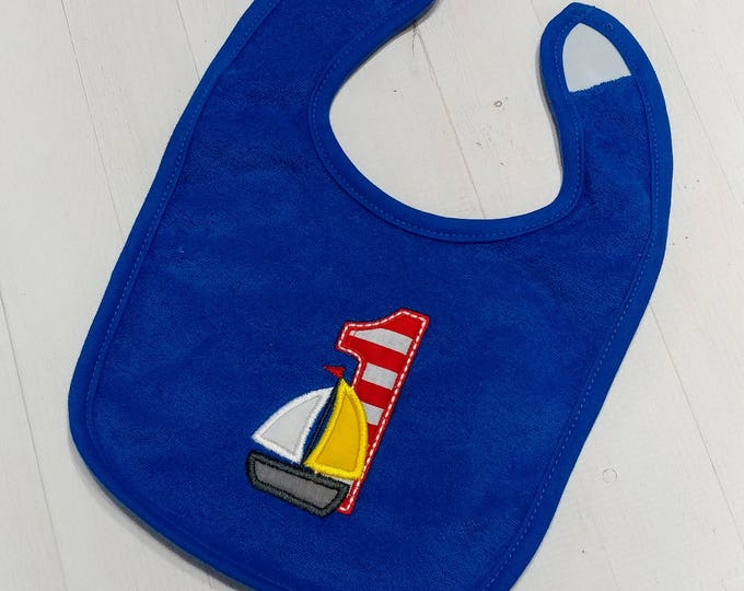 Sail boat with number one applique on royal blue embroidered Koala Baby cloth baby bibs for 6-12 month old boys