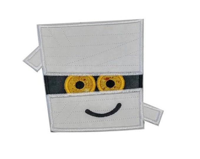 White mummy face with spooky yellow eyes Halloween iron on applique