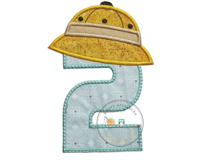 Boy's, number two geometric-shaped fabric trimmed in baby blue beneath large, safari/zoo hat in yellow-speckled print and trimmed with Khaki