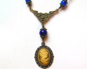 Bronze colour steampunk, victorian, goth necklace with blue glass beads and cameo pendant.