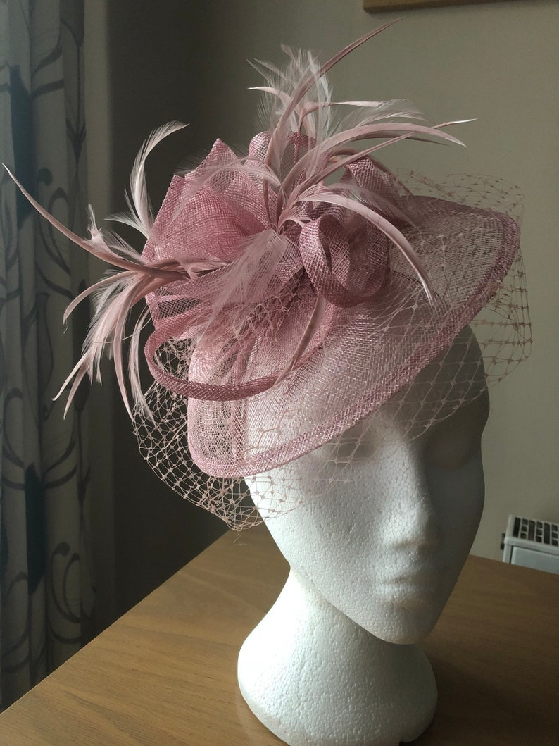 Heather Dusty Pink Fascinator in Sinamay with centre of pleated sinamay and feathers  with a twist of sinamay and delicate veil on a hairban