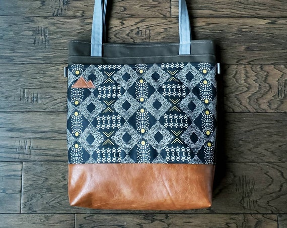 Large tote/Black, white & olive mudcloth print/Caramel brown vegan leather/Olive green bull denim/Gray canvas straps/4 pockets/MTN patch