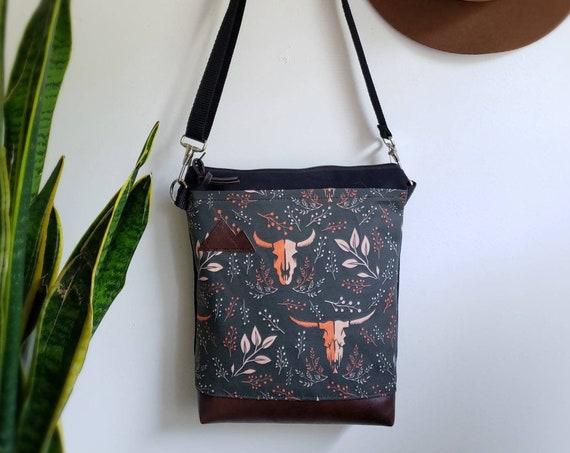 Medium crossbody/Keep it wild print front = pocket/Black zipper/Black canvas reverse/Black nylon adjustable strap/Mountain or Montana patch