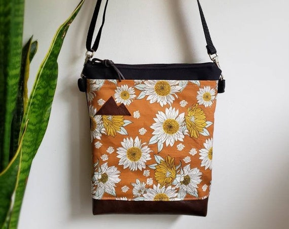 Medium crossbody/Orange sunflower print front = pocket/Black zipper/Black canvas reverse/Black nylon adjustable strap/Mountain or MT patch