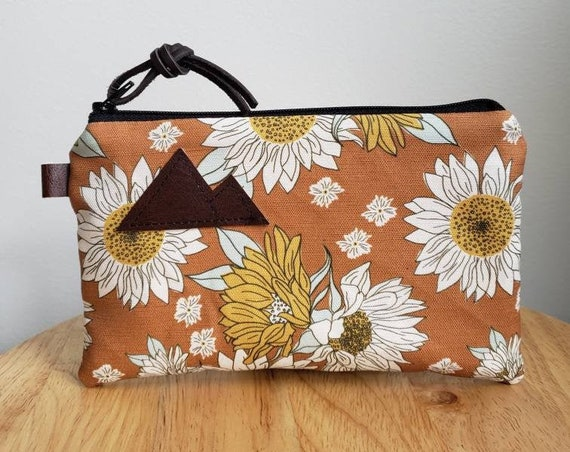 3 size options/Orange sunflower print = front and back/Natural canvas liner/Black zipper/Mountain or Montana patch