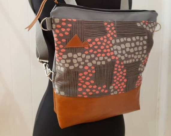 Convertible crossbody backpack/Flathead lake print in peach & grays=2 front pockets/Vegan leather/Gray canvas shell/White zipper/MT or MTN