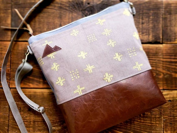 Large crossbody/Taupe & gold mud cloth print/2 front pockets/Dark brown vegan leather/Gray canvas back/White zip/Adjustable gray nylon strap