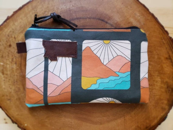 3 size options/Montana Soul print pouch/printed front and back/Natural canvas liner/Black zipper/Mountain or Montana patch