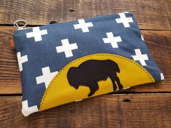 A new day bison clutch in 3 size options/Navy & white swiss cross print front and back/Natural canvas liner/White zipper/Wool felt applique