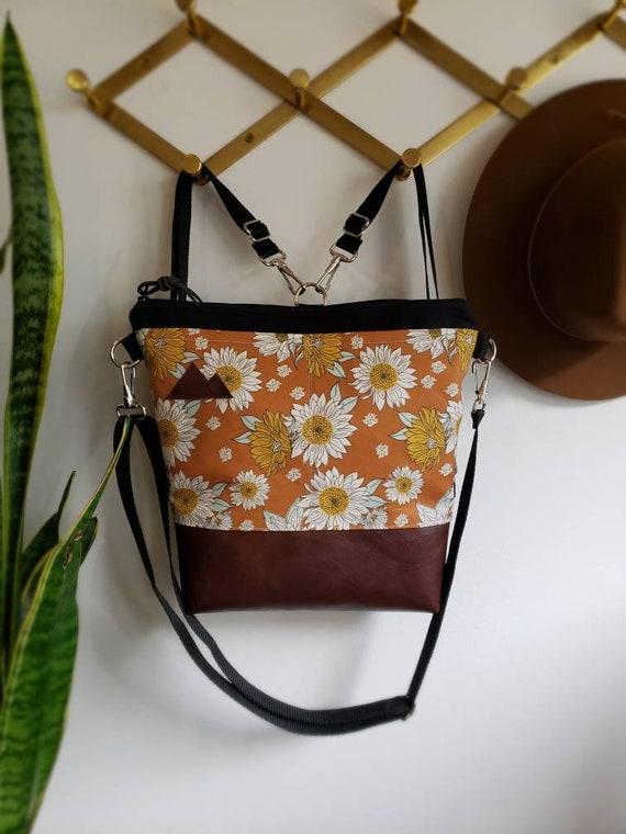 Convertible Backpack/Crossbody/Orange sunflower print=2 front pockets/Black canvas/Black zip/Black adjustable nylon straps/MT or Mountain