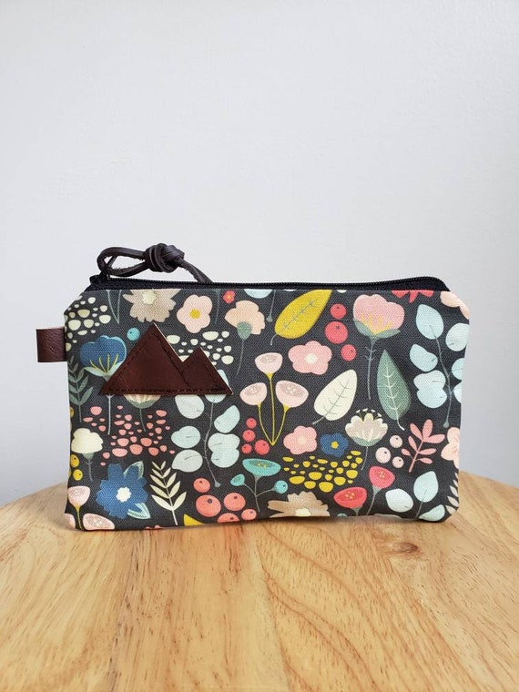 3 size options/Bold floral print = front and back/Natural canvas liner/Black zipper/Mountain or Montana patch