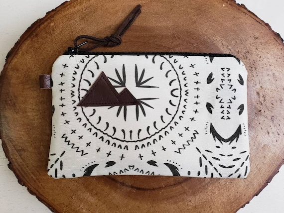Available in 3 sizes/Ivory & black bohemian print front and back/Black zipper/Brown suede zipper pull/Montana or mountain patch