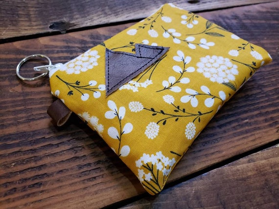 Lightweight cotton/Mustard yellow floral print front and back/Natural canvas liner/White zipper/Silver key ring zipper pull/In 3 sizes