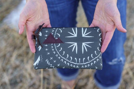 Available in 3 sizes/Charcoal gray bohemian print front and back/Black zipper/Brown suede zipper pull/Montana or mountain patch