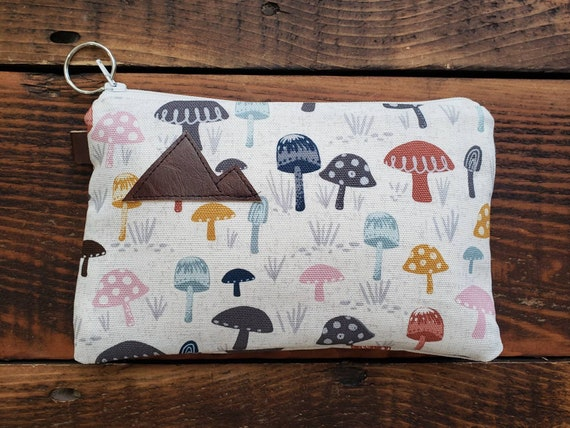 Mushroom pouch 3 size options/printed front and back/Natural canvas liner/White zipper/Mountain or Montana patch/Vegan leather details