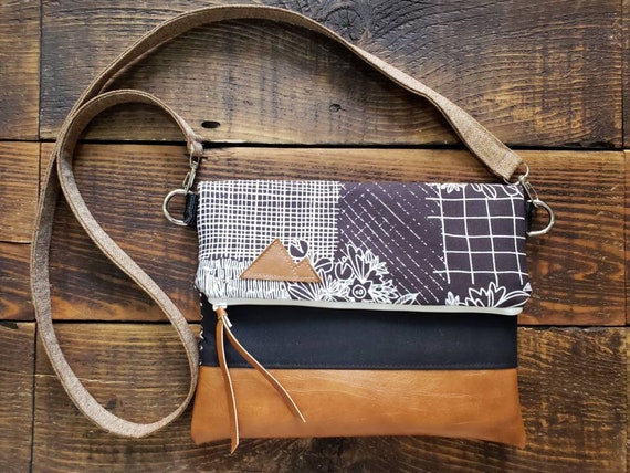 Foldover Crossbody/Plum & white garden print/Black canvas reverse/Vegan leather details/Brown linen strap/White zipper/Montana or MTN patch
