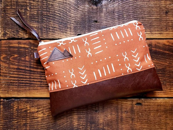 Grab & Go Clutch/Lightweight cotton rust mud cloth print/White zipper/Vegan leather details/Montana or Mountain patch/Natural canvas liner