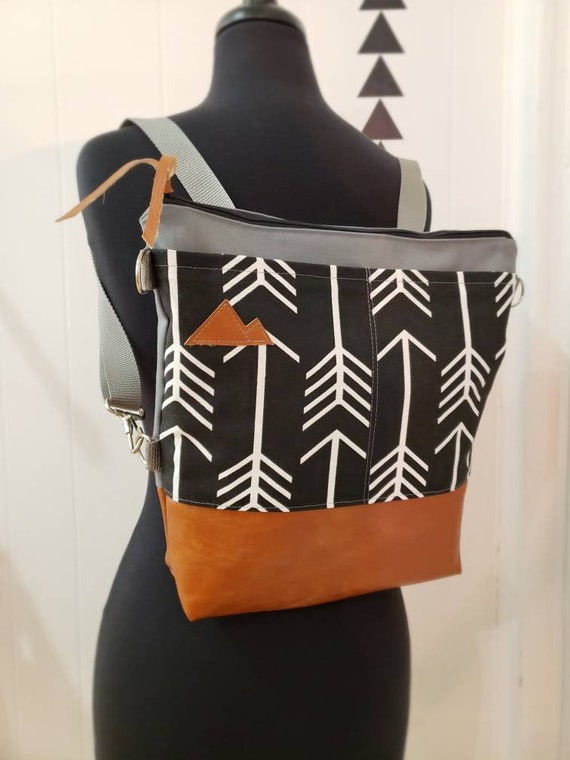 Convertible crossbody backpack/Black+white arrows print=2 front pockets/Vegan leather/Gray canvas shell/White zipper/Montana or Mountains