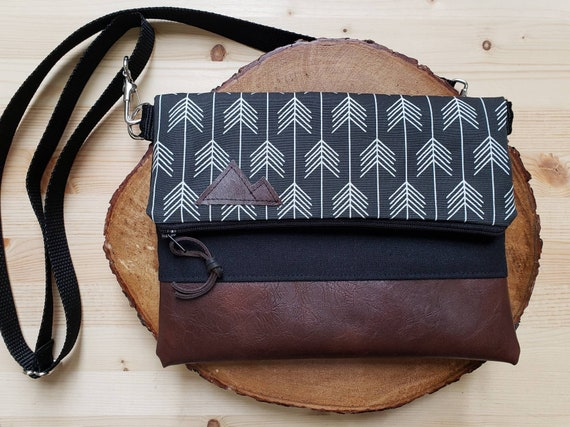 Foldover crossbody/Feathered arrows black print/Black zipper/Black canvas reverse/Black nylon adjustable strap/Mountain or Montana patch