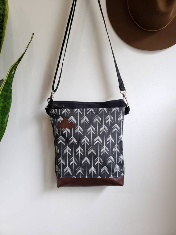 Medium crossbody/True North print in black with white arrows = front pocket/Black zipper/Black canvas reverse/Black nylon adjustable strap