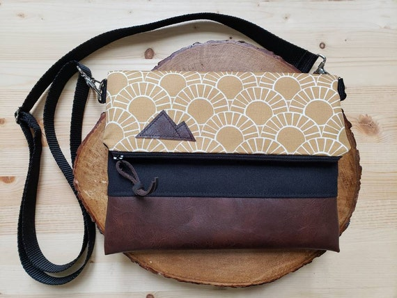 Foldover crossbody/Stay Golden print/Black zipper/Black canvas reverse/Black nylon adjustable strap/Mountain or Montana patch