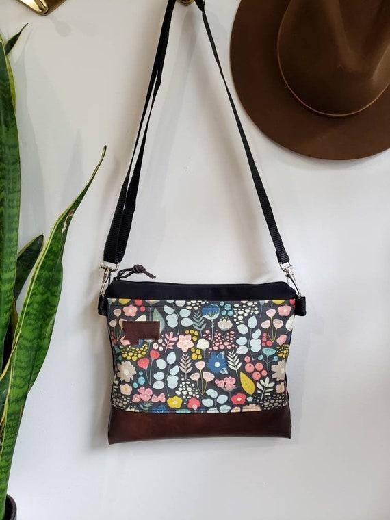 Small crossbody/Bold floral print = front pocket/Black zipper/Black canvas reverse/Black nylon adjustable strap