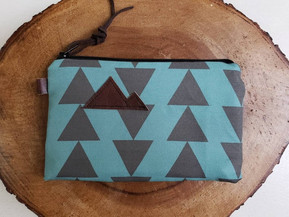 Available in 3 sizes/Teal & charcoal triangles print front and back/Black zipper/Brown suede zipper pull/Montana or mountain patch