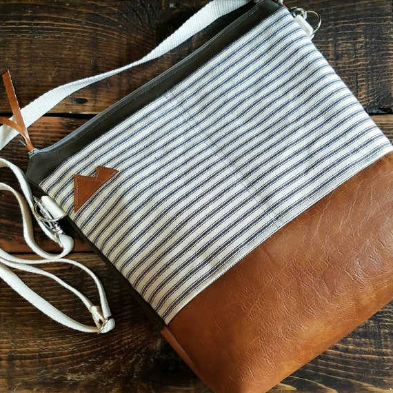 Large Crossbody/Navy & ivory ticking=2 front pockets/Caramel brown vegan leather/Gray zip/Adjustable strap/Mountain patch/Olive green denim