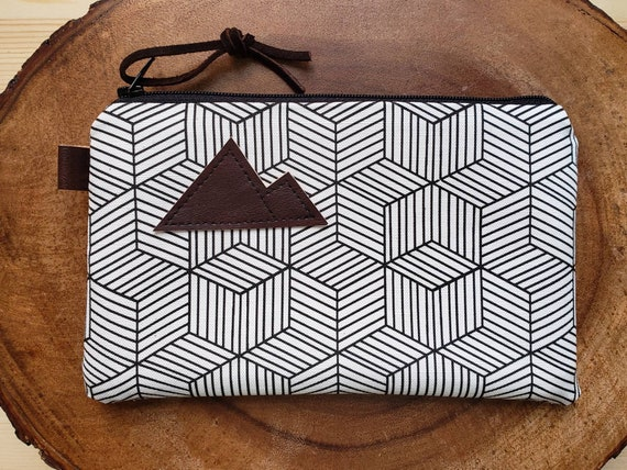 White & black geo pouch/3 size options/printed front and back/Natural canvas liner/Black zipper/Mountain or Montana patch/Vegan leather