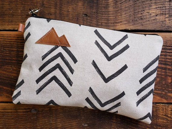 Medium Clutch 5.5x9.5in./North and south mud cloth print front and back/Natural canvas liner/White zip/MT or MTN patch/Vegan leather details