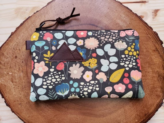 Bold floral pouch/3 size options/printed front and back/Natural canvas liner/Black zipper/Mountain or Montana patch/Vegan leather details