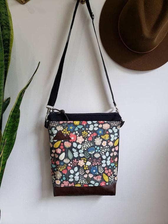 Medium crossbody/Bold floral print = front pocket/Black zipper/Black canvas reverse/Black nylon adjustable strap