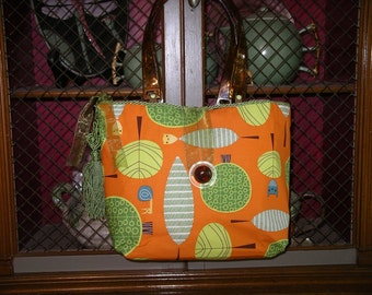 Orange and green print handbag with tortoise-shell handles and buttons