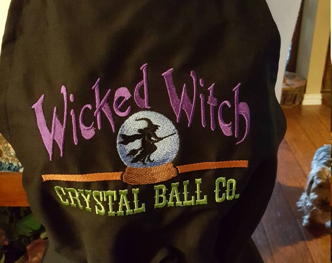 "Novelty Adult Apron with ""Wicked Witch Crystal Ball Company"" embroidery design"