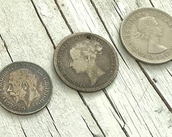 British silver coins. Set 1 — Queen Victoria and George V, threepences. Set 2 — Queen Victoria, George V and Queen Elizabeth II coins.